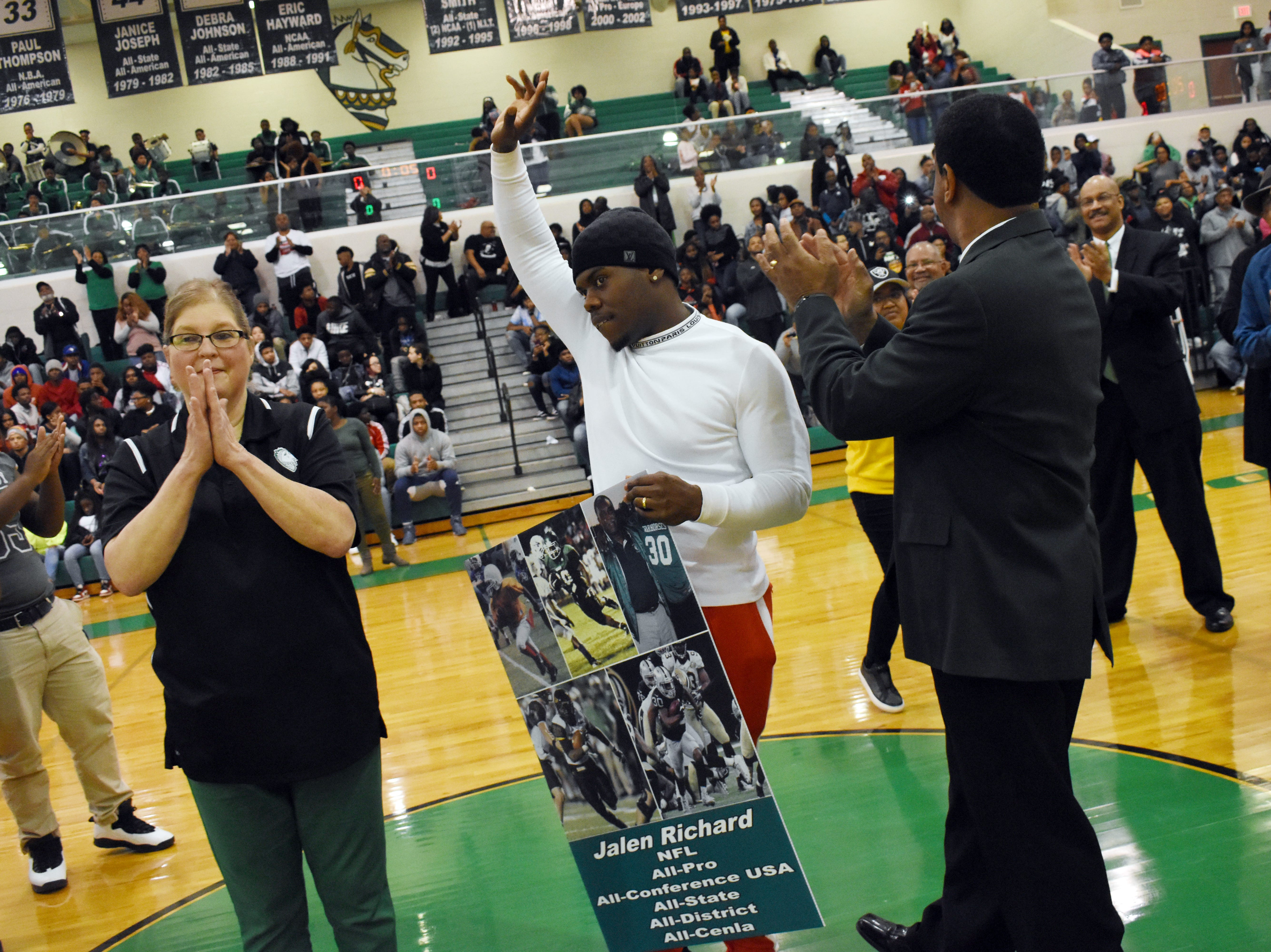 Oakland Raiders running back Jalen Richard (center) watches as a banner is raised retiring his jersey at Peabody Magnet High School where he graduated in 2012. With Richard are Peabody principal Jamie Henagan (left) and Peabody athletic director and head basketball coach Charles Smith (right). Richard's jersey was retired in a ceremony Friday, Jan. 25,2019 at Peabody Magnet High School. While at Peabody, Richard made the LSWA Class 4A All-State first team as a junior, and the All-Cenla and All-District first teams as a sophomore and a junior. Richard graduated from the University of Southern Mississippi in 2016. Richard signed a contract with the Raiders in 2016 after being invited to attend a rookie minicamp.
