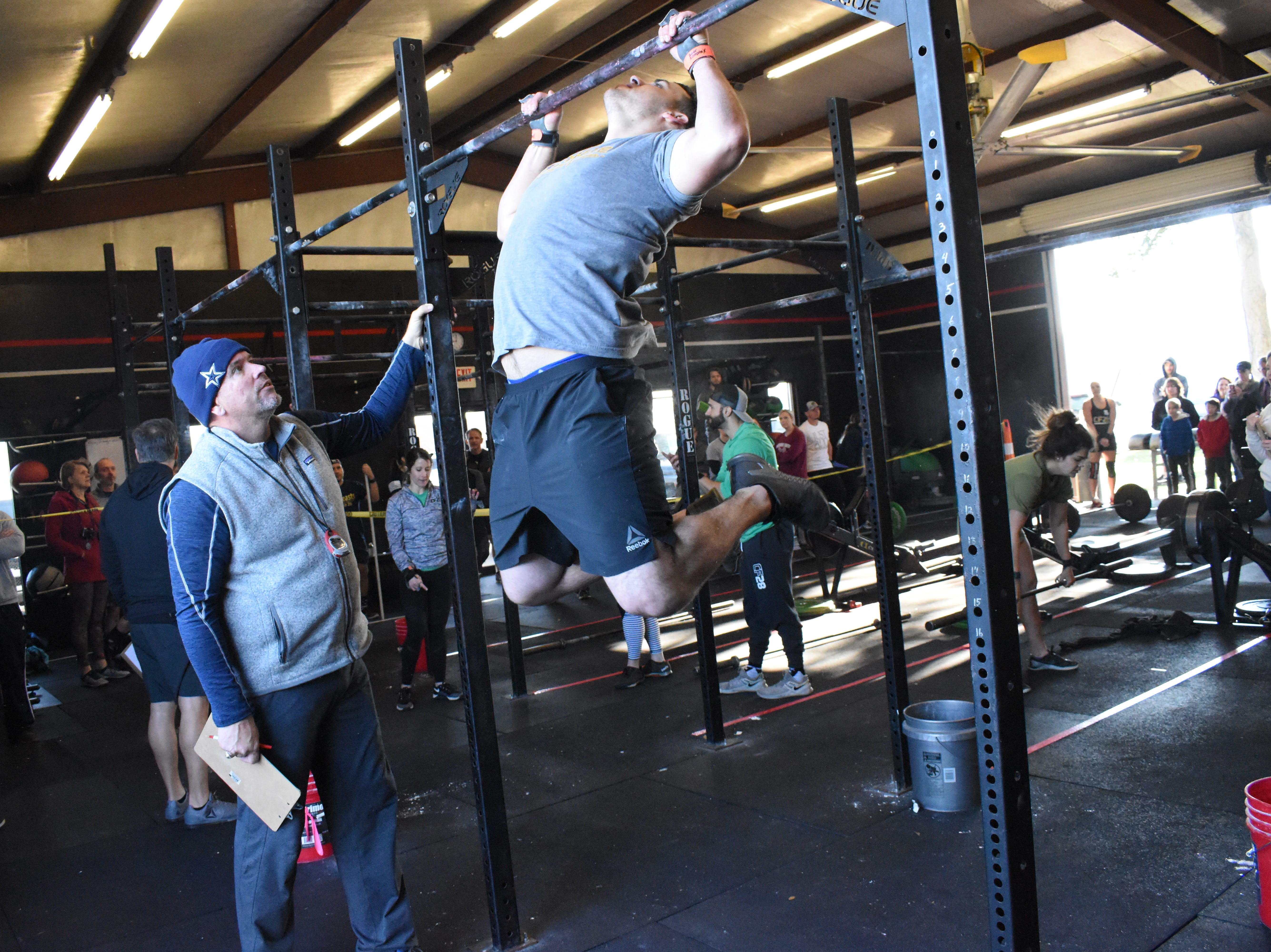 Fred Ruggles (left), a judge in the Iron Boot Classic, watches Nick Luneau, of Iron Boot, complete a set of butterfly pull-ups in the Iron Boot Classic. Twenty teams from six CrossFit affiliates in the area competed in the Iron Boot Classic  Saturday, Jan. 26, 2019 at the Iron Boot, formerly CrossFit Alexandria. Each team consisted of two men and two women who competed in five heats throuighout the day. Some of the exercises they performed were classic workouts such as deadlifts, burppees, wall balls and thrusters. William Albritton, owner of Iron Boot, said the competition involved the classic movements so everyone who works out could participate.