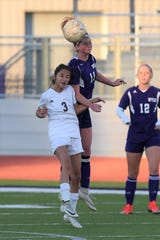 Wylie's Shaelyn Ward (11) goes over a Midland Lee player to head the ball at Bulldog Stadium on Friday, Jan. 25, 2019. The Lady Bulldogs won 2-0.