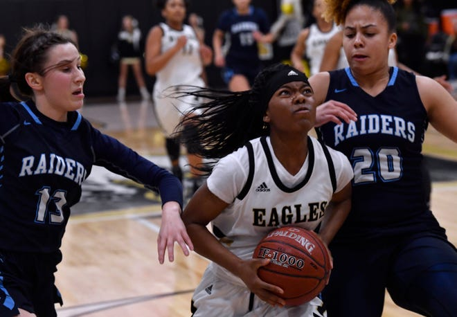Abilene High's Trakenya Roberson is flanked on both sides by Hurst Bell's Claire McDonald (left) and Madison Bishop during Friday's basketball game in the Eagle Gym Jan 25, 2019. Final score was 58-51, Hurst Bell.