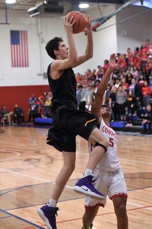 Wylie's Austin Brewer (4) goes up over Aeneas Favors (5) for a basket at Cougar Gym on Friday, Jan. 25, 2019. The Bulldogs won 58-47.