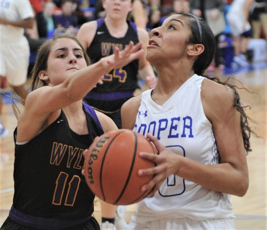 Wylie's Madi Latham, left, defends as Cooper's Keiana Kemp drives to the basket. Wylie beat the Lady Cougars 64-42 in the District 4-5A game Friday, Jan. 25, 2019, at Cougar Gym.