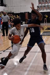 Abilene High's Jalen McGee pushes past Hurst Bell's Nazir Brown during Friday's game in the Eagle Gym Jan. 25, 2019. Final score was 64-52, Abilene High.