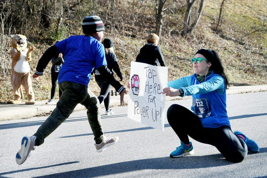 """Amy Kett holds a sign to encourage runners during the toughest part of the Asheville Hot Chocolate 10K and 5K races as Devin Smith, 10, reaches for a """"power up"""" Jan. 26, 2019 at Isaac Dickson Elementary School."""