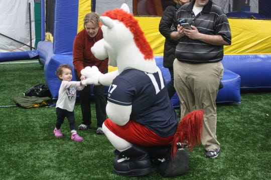 Charlee Cordero, 2, of Owego gives Rowdy the Rumble Pony a hi-5 at 434 Sportsplex's inaugural Winterfest Friday evening.