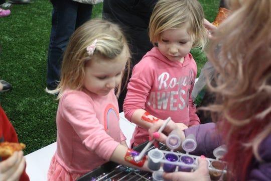 Hanna Bestle, 2, and Heather Bestle, 3, both of Vestal, get glitter tattoos at 434 Sportsplex's inaugural Winterfest Friday evening.