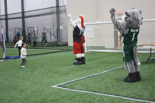 Rowdy the Rumble Pony and Baxter the Bearcat play inside 434 Sportsplex at the inaugural Winterfest Friday evening.