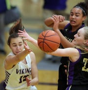 North Kitsap's Katie Komar (left) makes a pass around a pair of Sequim defenders under the basket in Poulsbo on Friday, January 25, 2019.