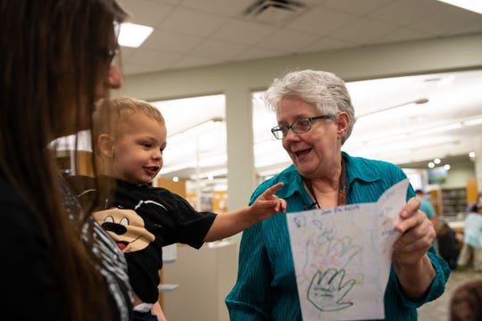 """Everett Cockrell hands librarian Jean Meadors a card before her last Miss Jean's """"Story Time Kids"""" at the Owen R. Hopkins Public Library on Saturday, Jan. 26, 2019. Miss Jean is retiring after 30 years as a librarian."""