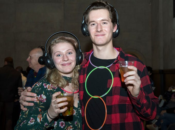 Jenny Clemens and Lee Coryea take advantage of free glow stick necklaces at the 90s-themed silent disco during Art After Dark at the Cincinnati Art Museum Friday, January 25, 2019 in Cincinnati, Ohio.