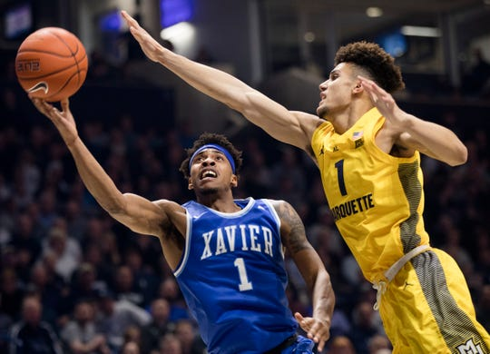 Xavier Musketeers guard Paul Scruggs (1) shoots around Marquette Golden Eagles forward Brendan Bailey (1) in the first half of the NCAA men's basketball game between Xavier Musketeers and Marquette Golden Eagles on Saturday, Jan. 26, 2019, at Cintas Center in Cincinnati.