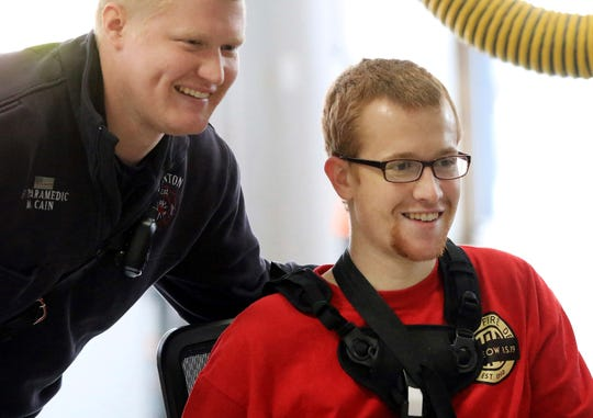 Clinton Fire Department paramedic Matt Cain, left, poses for a picture with his brother Clinton firefighter Adam Cain during a homecoming celebration at the Central Fire Station, Friday, Jan. 25, 2019, in Clinton, Iowa. Cain was released from the University of Iowa Hospitals on Friday and driven to the Central Fire Station in Clinton for the first time since being seriously injured while battling a grain bin fire at the Archer Daniels Midland plant in Clinton on Jan. 5.