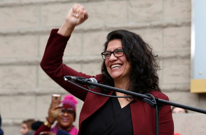 Rep. Rashida Tlaib acknowledges the applause from the  crowd of people gathered for the Women's March and rally inside the Ford Rotunda inside the Charles H. Wright Museum of African American History in Detroit on Saturday, January 19, 2019.