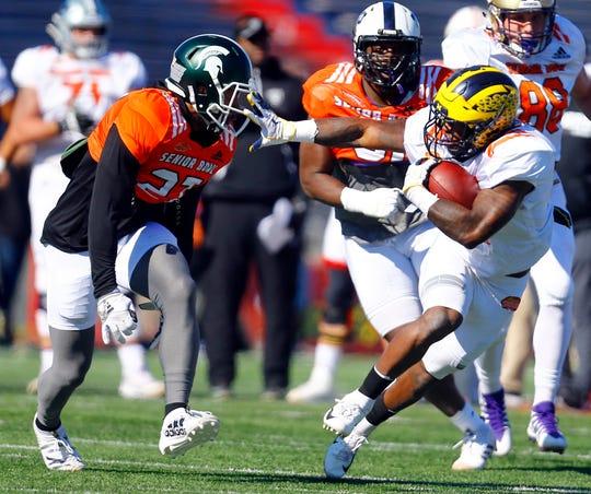 Michigan's Karan Higdon stiff arms Michigan State's Khari Willis during practice for the Senior Bowl game, Thursday in Mobile, Ala.
