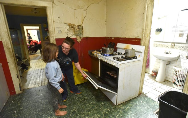 Grace Anderson gives daughter Emily, 7, a cooking tip in their Delray neighborhood home in Detroit.