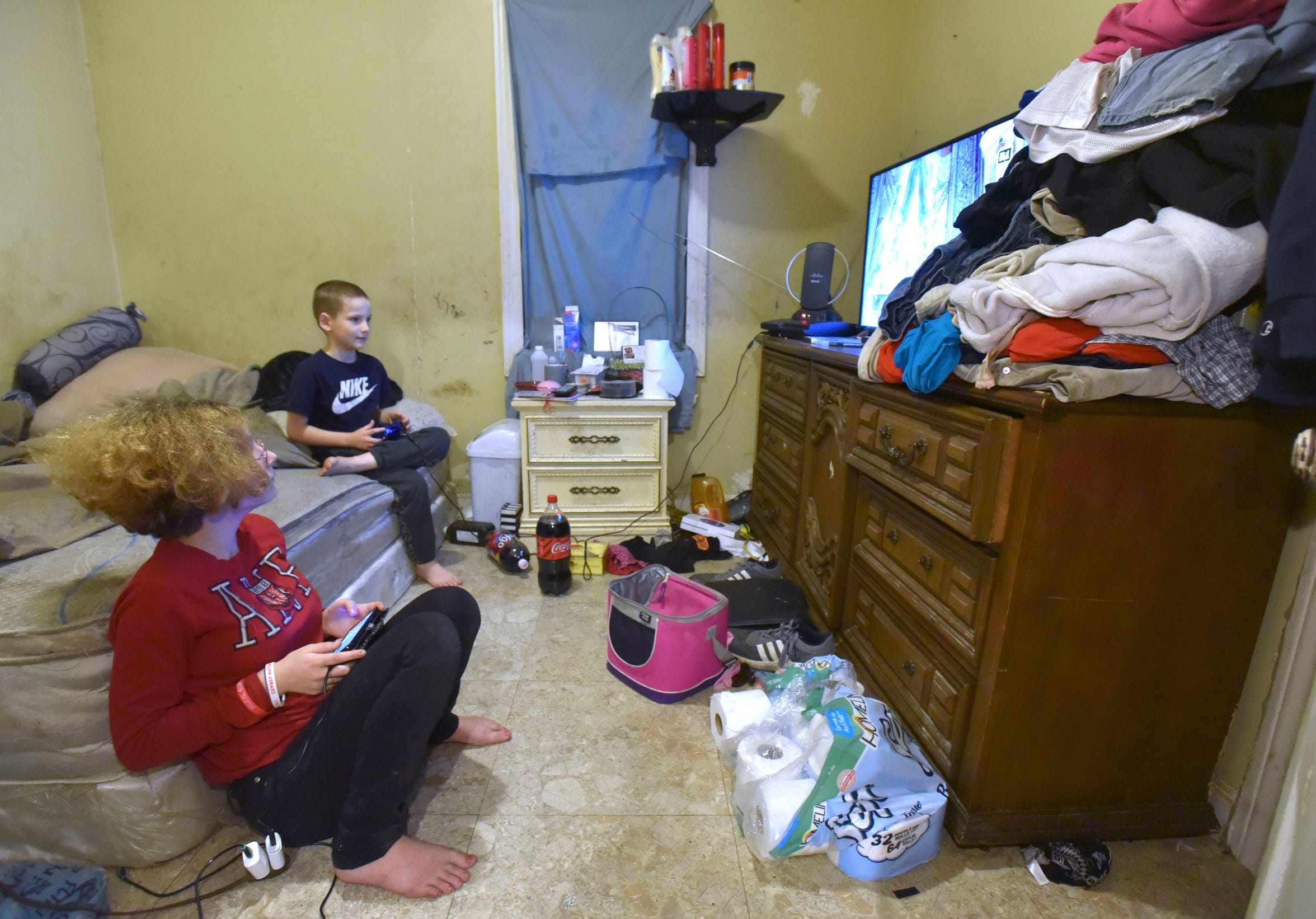 Shashana Gutierrez, left, 14, and Robert 'Chuncky' Anderson,  9,  play video games in the parents' bedroom.
