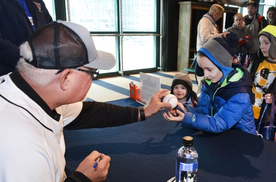 Tigers manager Ron Gardenhire signs a baseball for Jackson Farrell during TigerFest.