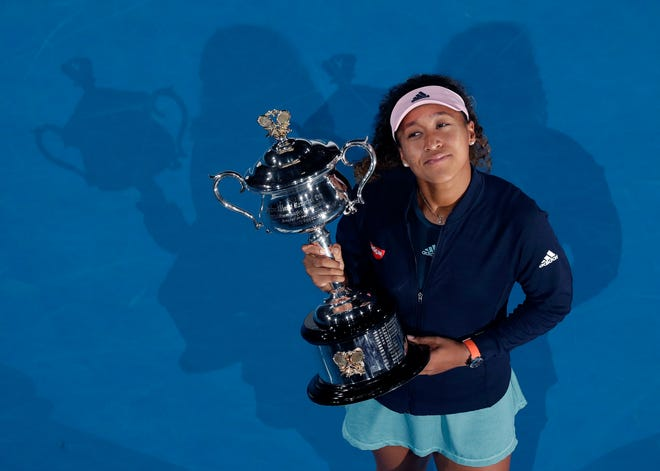 Naomi Osaka holds her trophy after defeating Petra Kvitova in the Australian Open.
