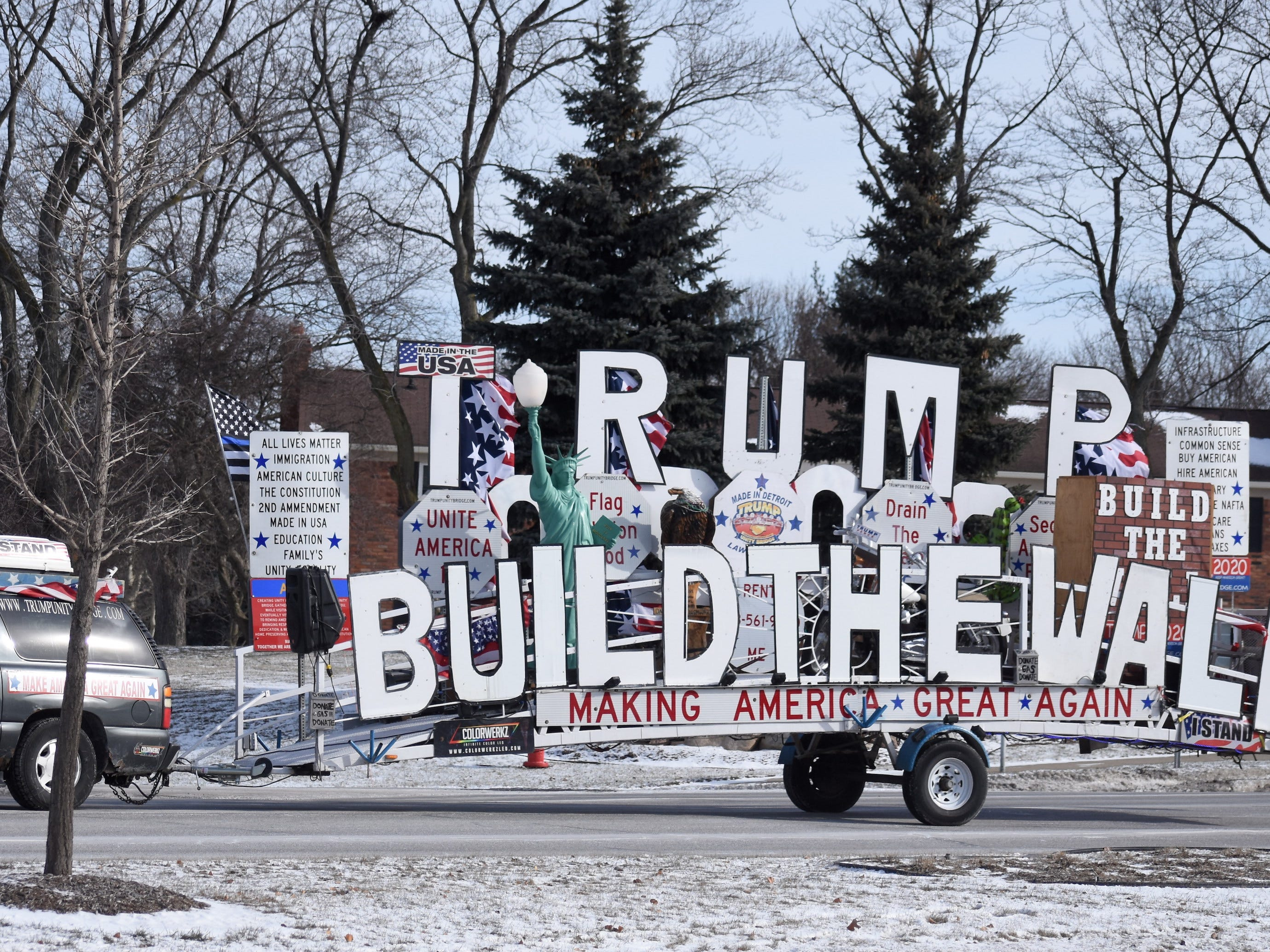 A vehicle hauling a rolling Trump Wall endorsement motors north on Woodward.