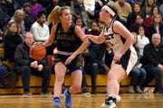 Birmingham Marian guard Olivia Moore (12) is guarded by Farmington Hills Mercy guard Annie Treharne (31) during the first quarter.