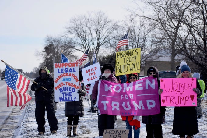 """Protestors from various groups, including """"Women for a Safe America"""" and """"Women for Trump,"""" line Woodward Avenue for a """"Build the Wall"""" rally at the Oakland County Republican Party offices in Bloomfield Hills, Michigan on January 26, 2019."""