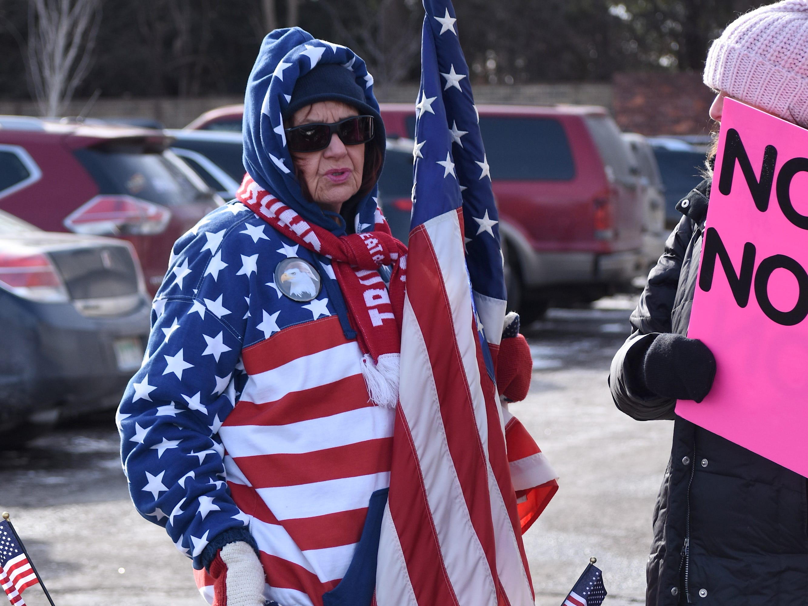 Elizabeth Fohey, left, of Troy, chats with another demonstrator outside the Oakland County Republican Party offices.