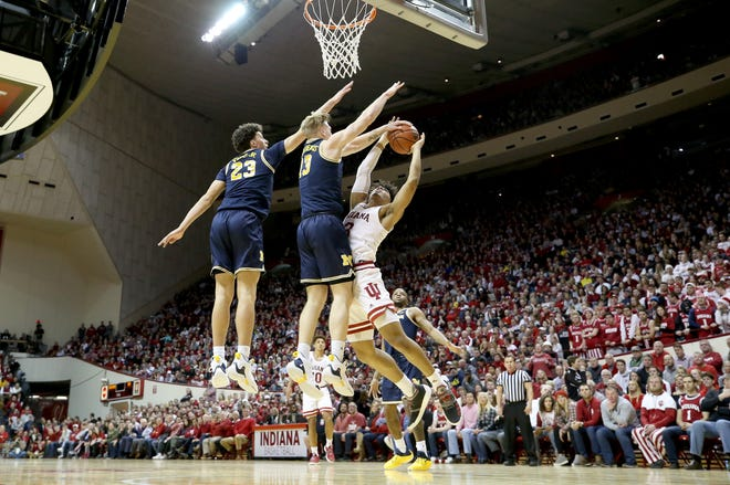 Brandon Johns and Ignas Brazdeikis of the Michigan Wolverines defend the shot of Justin Smith of the Indiana Hoosiers.
