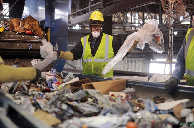 Joe Sowders (center) takes plastic bags off the line as he opens them and sorts through recyclables at Tri-State Resource Recovery on Thursday, May 1, 2014. Since the citywide curbside recycling program changed, Tri-State has seen a 50 percent increase in residential and commercial recycling.