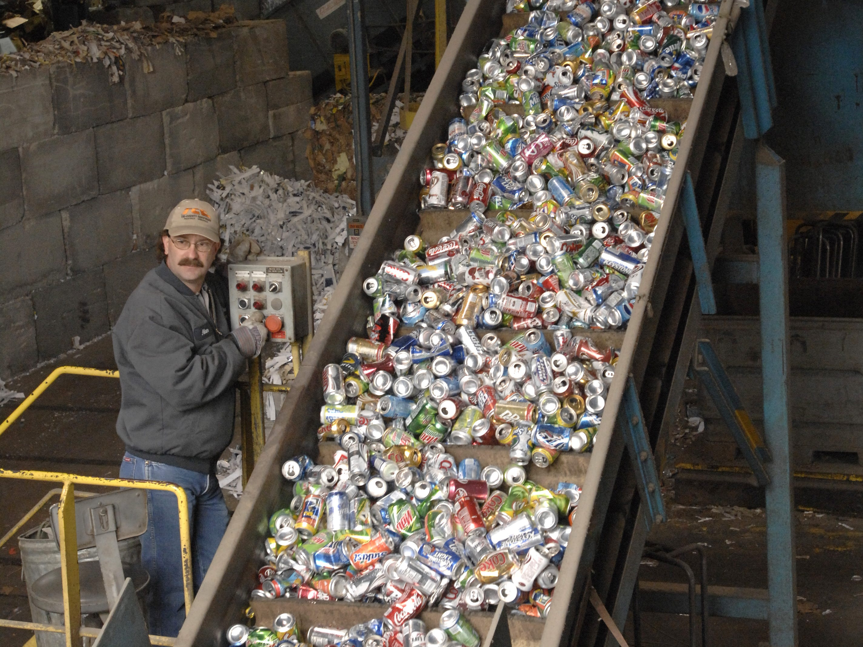 Alan Wayman operates a conveyor as aluminum cans are delivered for recycling Wednesday at Tri-State Resource and Recovery April 18, 2007. All of the curb side recycling ends up at the huge warehouse where it is baled and shipped to other recyclers. The facility handles aluminum, glass, plastic bottles 1 and 2, newspaper, mixed paper, cardboard, books, and steel cans.