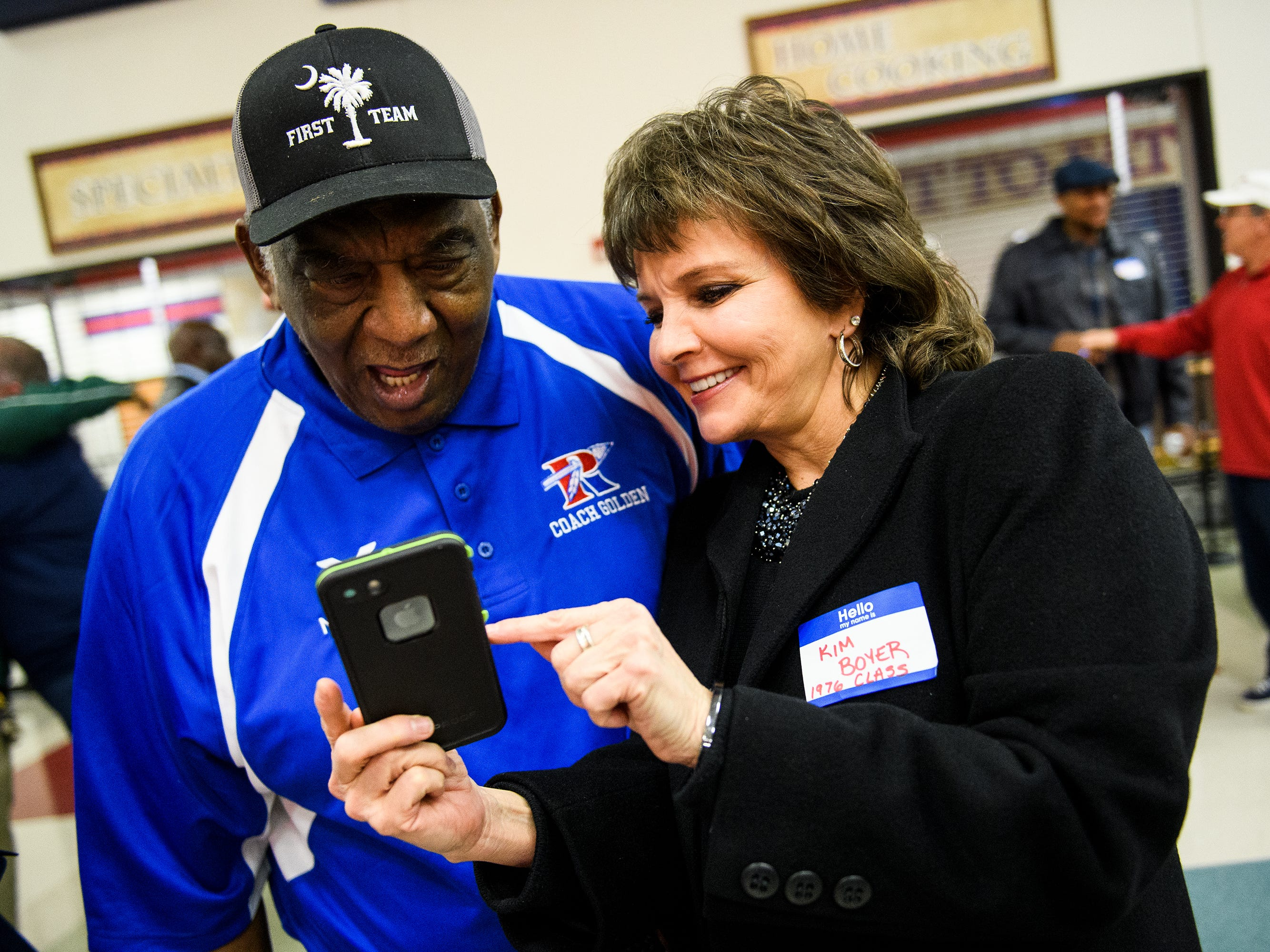 Kim Boyer shows former Riverside basketball coach Louie Golden an old photograph on her phone during an honoring service for Golden on Friday, Jan. 25 2019 at Riverside High School.