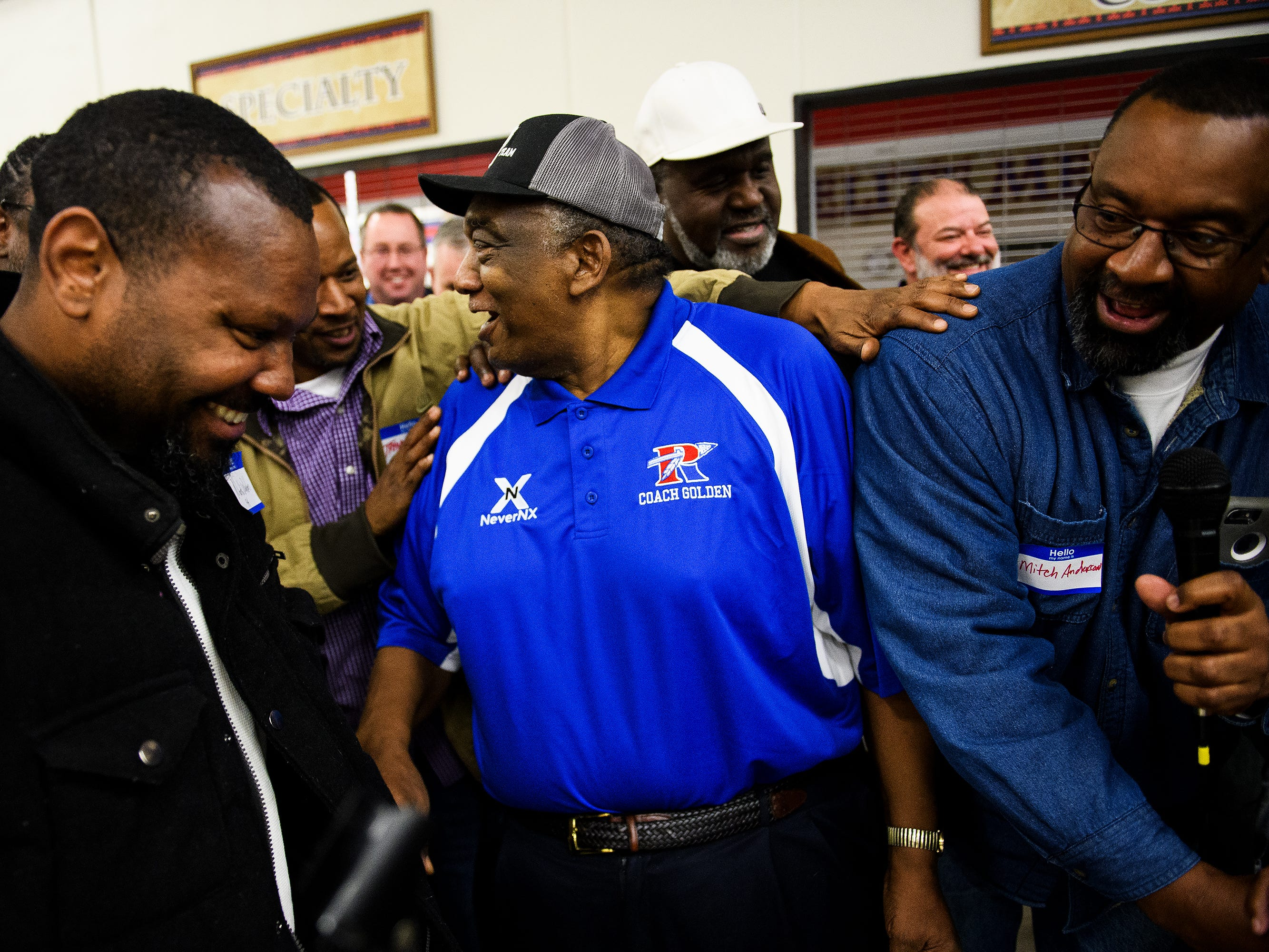 Louie Golden is surrounded by several of his former basketball players during a night honoring his legacy as one of South Carolina's winningest prep basketball coach at Riverside High School on Friday, Jan. 25 2019.