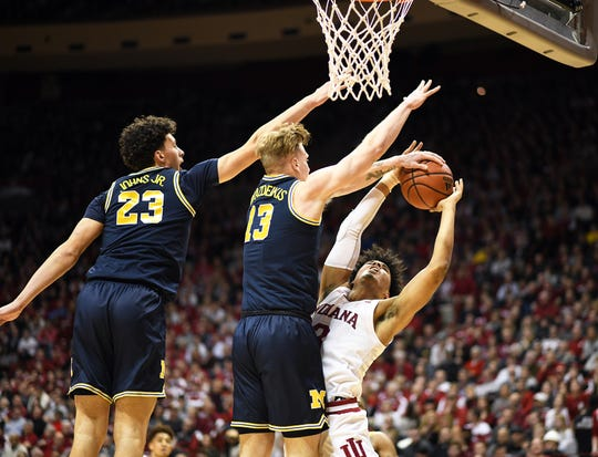 Indiana's Justin Smith is blocked by Michigan's Ignas Brazdeikis (13) in Bloomington, Ind., on Friday.