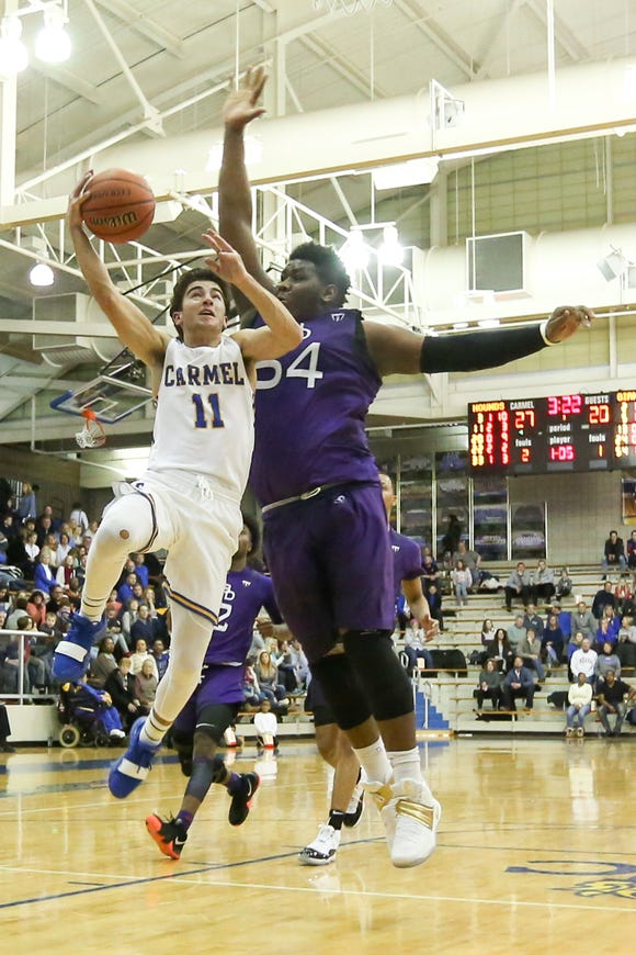 Carmel's Luke Heady (11) tries to drive the basket around Ben Davis Dawand Jones (54) during the second half of Carmel vs. Ben Davis High School varsity basketball held at Carmel High School, January 25, 2019.
