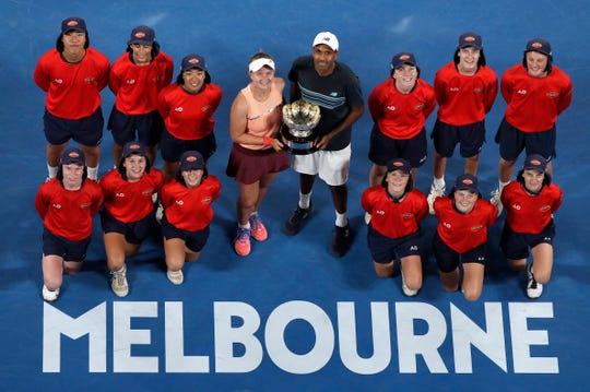 Barbora Krejcikova of the Czech Republic and United States' Rajeev Ram pose with their trophy and ball kids after defeating Australia's Astra Sharma and compatriot John-Patrick Smith in the mixed doubles final at the Australian Open tennis championships in Melbourne, Australia, early Sunday, Jan. 27, 2019. (AP Photo/Kin Cheung)