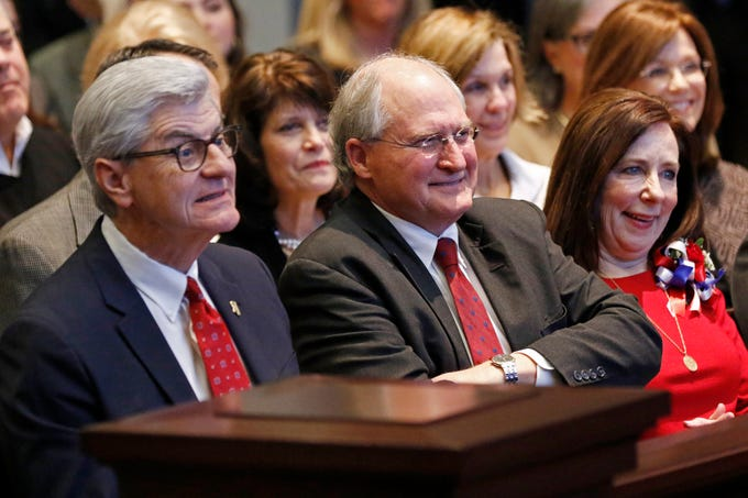 Mississippi Gov. Phil Bryant, left, state Supreme Court Chief Justice William L. Waller Jr., center, and his wife Charlotte Waller, laugh during a retirement ceremony honoring Waller at the Mississippi Supreme Court chambers in Jackson, Miss., Friday, Jan. 25, 2019. Waller officially retires on January 31 after more than 21 years of service on the Supreme Court and 10 years as Chief Justice. (AP Photo/Rogelio V. Solis)