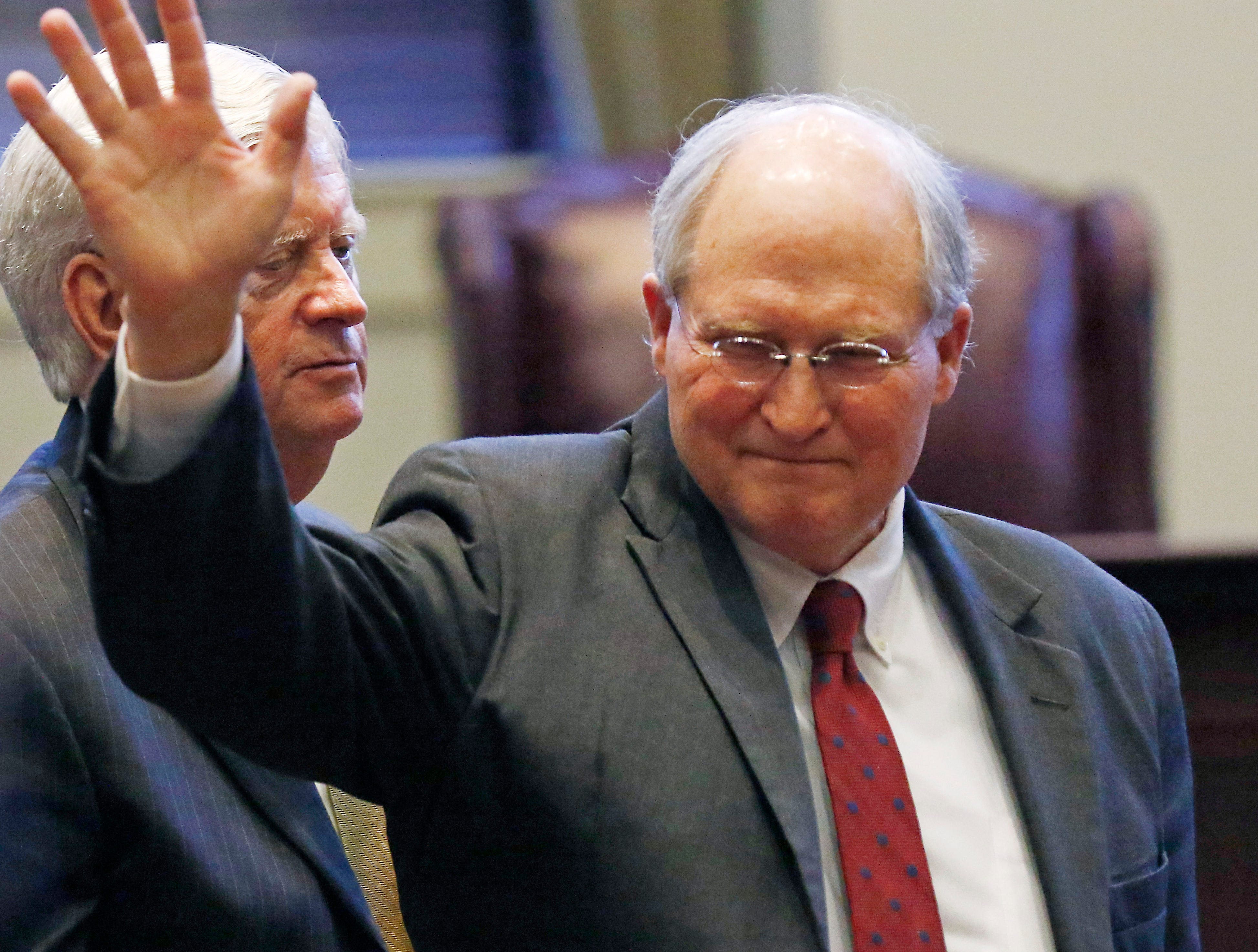 Presiding Justice Michael K. Randolph, left, stands beside state Supreme Court Chief Justice William L. Waller Jr., right, as he acknowledges the applause at his retirement ceremony in the Mississippi Supreme Court chambers in Jackson, Miss., Friday, Jan. 25, 2019. Waller officially retires on January 31 after more than 21 years of service on the Supreme Court and 10 years as Chief Justice. (AP Photo/Rogelio V. Solis)