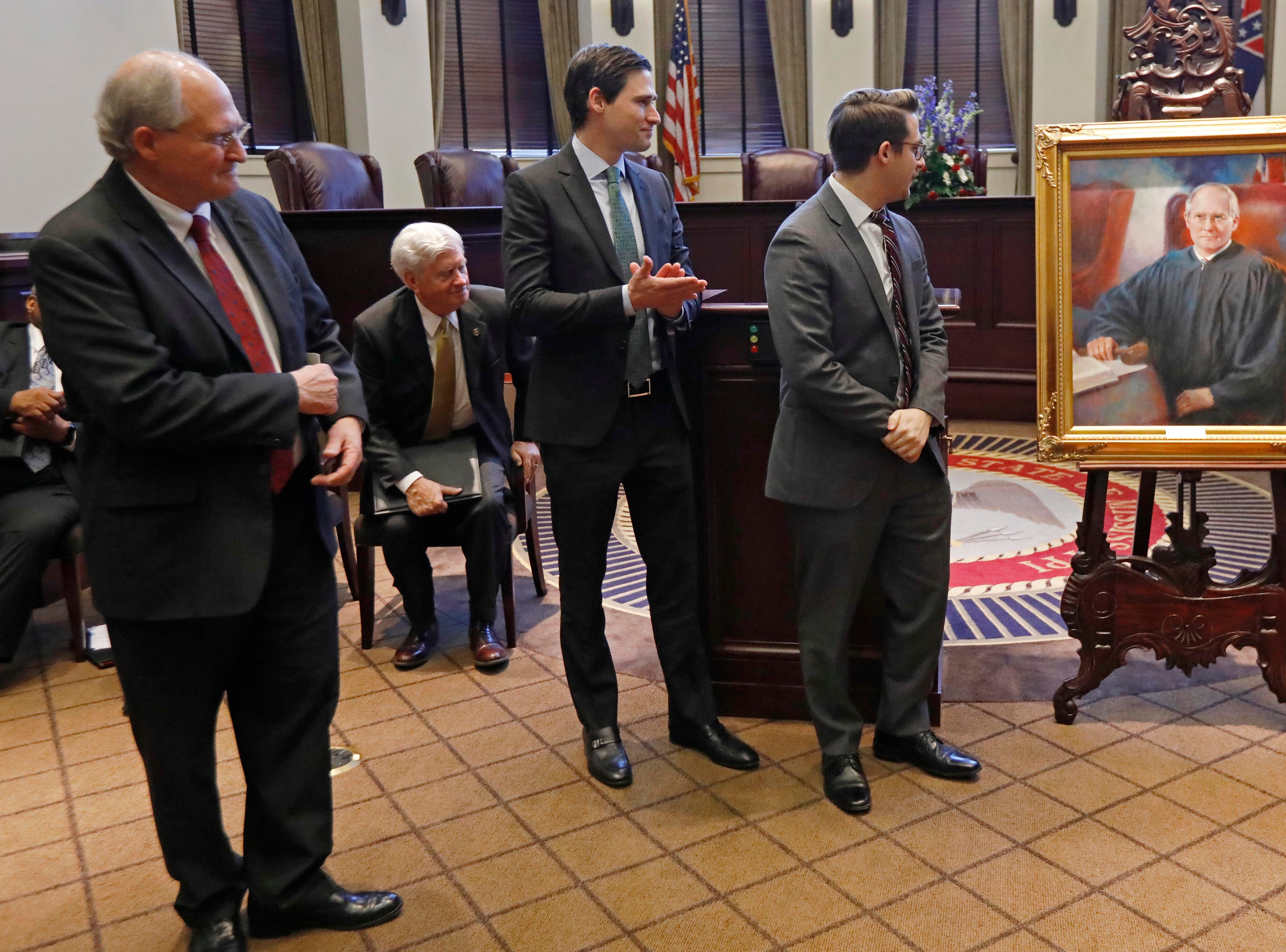 Mississippi Supreme Court Chief Justice William L. Waller Jr., left, watches as his sons Dr. William L. Waller III, second from left, brother Clayton Waller, center, assist their mother Charlotte Waller, right, as they unveil the chief justice's portrait during his retirement ceremony in the Supreme Court chambers in Jackson, Miss., Friday, Jan. 25, 2019. The portrait will be hanged in the courthouse with other chief justices' portraits. Waller officially retires on January 31 after more than 21 years of service on the Supreme Court and 10 years as Chief Justice. (AP Photo/Rogelio V. Solis)