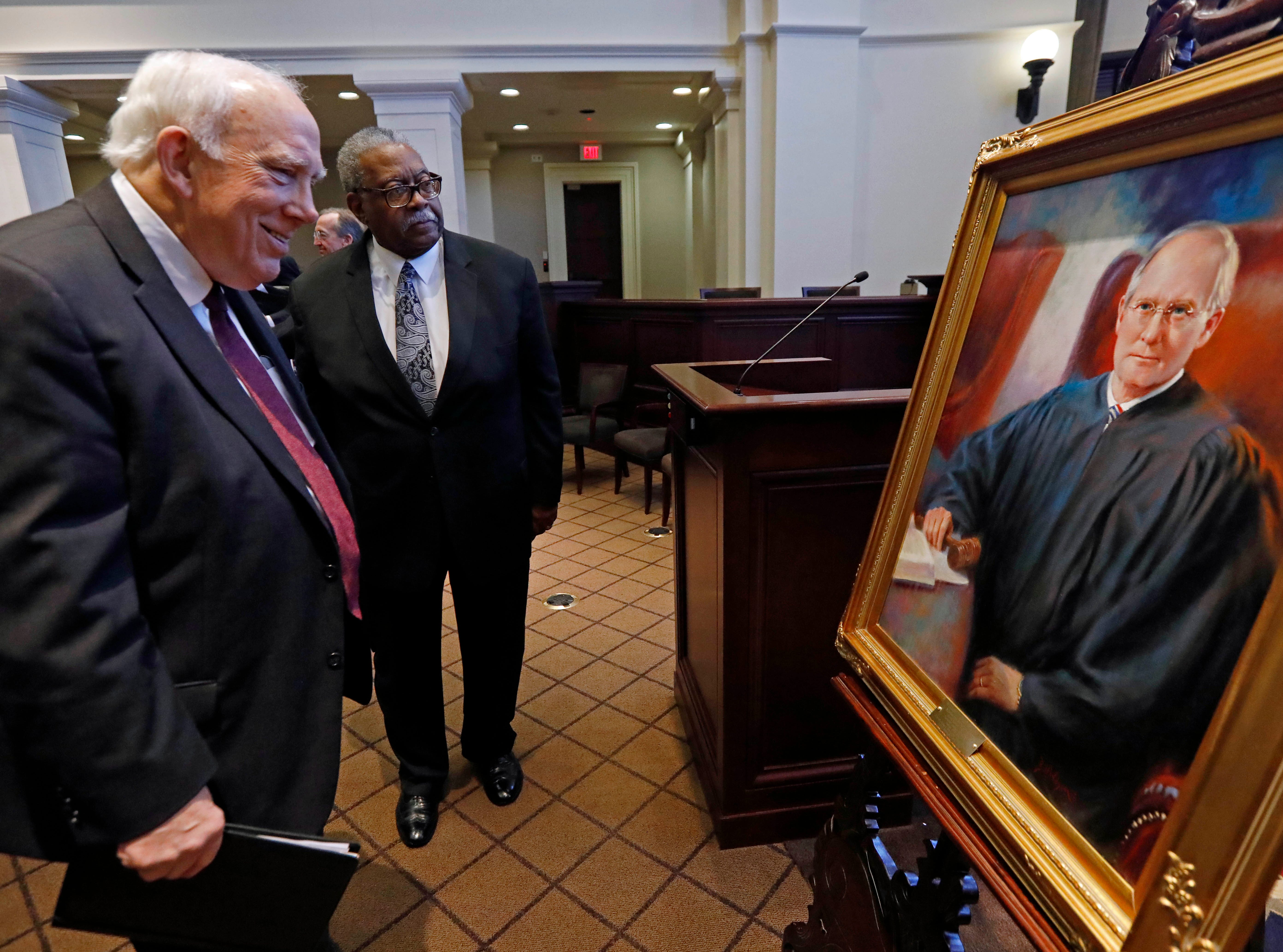 Presiding Supreme Court Justice James W. Kitchens, left, and Associate Justice Leslie D. King, inspect the portrait of Mississippi Supreme Court Chief Justice William L. Waller Jr., during a retirement ceremony honoring Waller at the Mississippi Supreme Court chambers in Jackson, Miss., Friday, Jan. 25, 2019. Waller officially retires on January 31 after more than 21 years of service on the Supreme Court and 10 years as Chief Justice. (AP Photo/Rogelio V. Solis)
