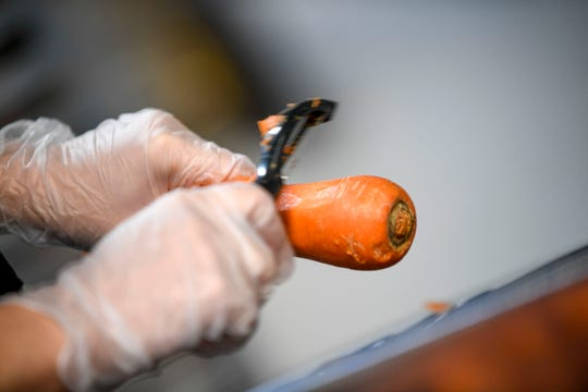 Tyanna Freeman, 17, a senior at Liberty Tech, skins carrots as a part of preparing them for use at Brooks Shaw's Old Country Store in Jackson, Tenn., on Friday, Jan. 25, 2019.