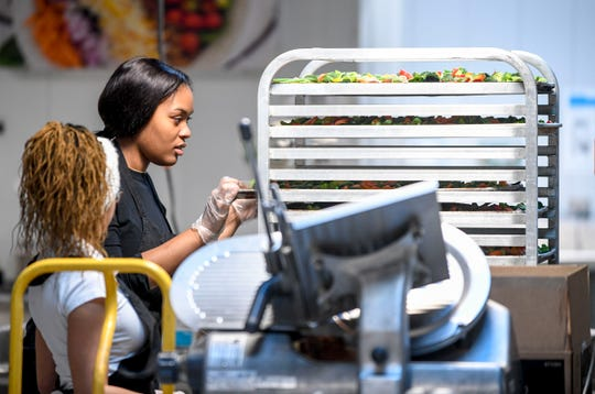 Toneice Bell, 16, a junior at Liberty, prepares trays of vegetables with Tyanna Freeman, 17, a senior at Liberty Tech, left, at Brooks Shaw's Old Country Store in Jackson, Tenn., on Friday, Jan. 25, 2019.