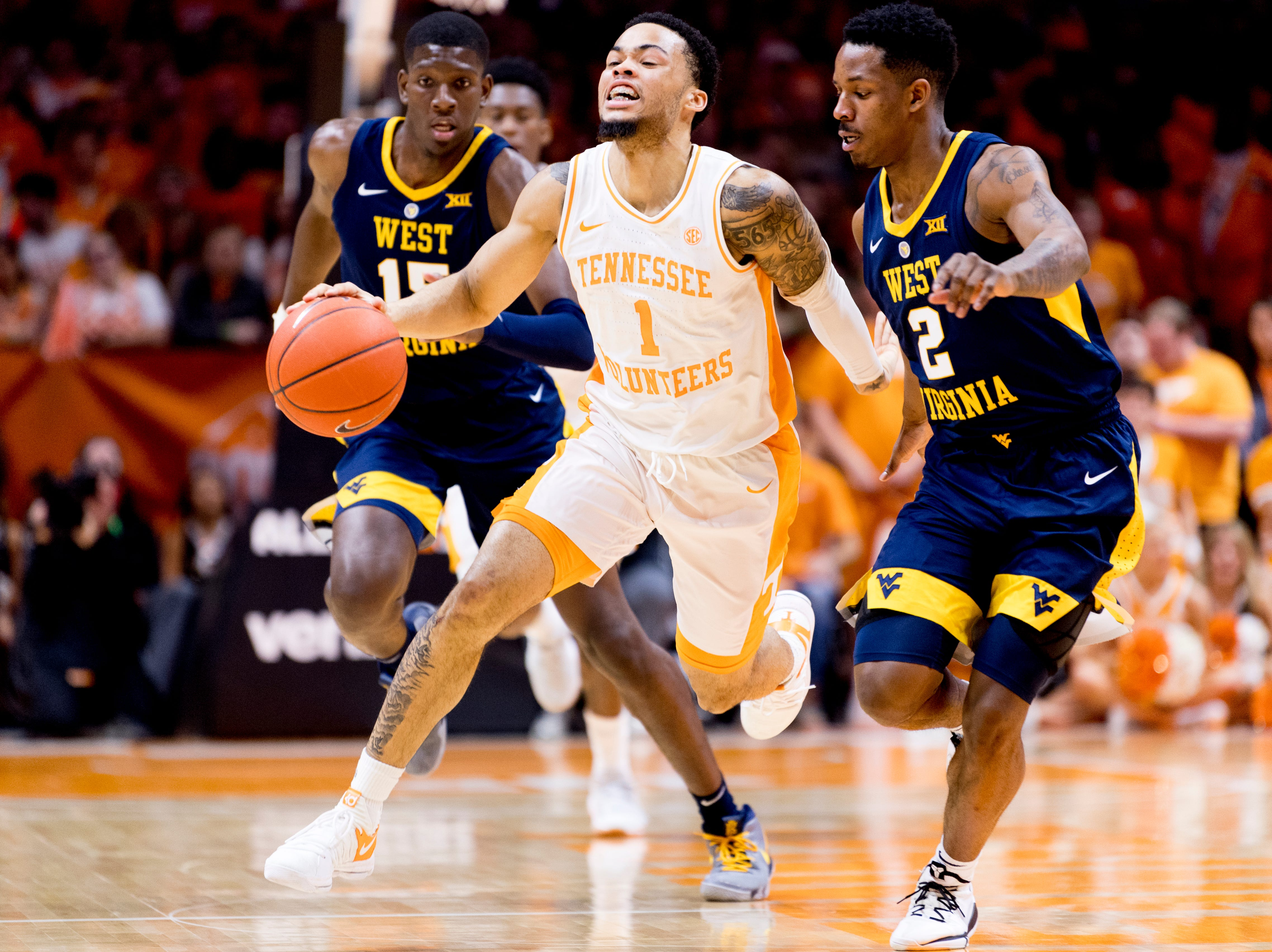 Tennessee guard Lamonte Turner (1) dribbles down the court as West Virginia guard Brandon Knapper (2) and West Virginia forward Lamont West (15) defend during a SEC/Big 12 Challenge game between Tennessee and West Virginia at Thompson-Boling Arena in Knoxville, Tennessee on Saturday, January 26, 2019.