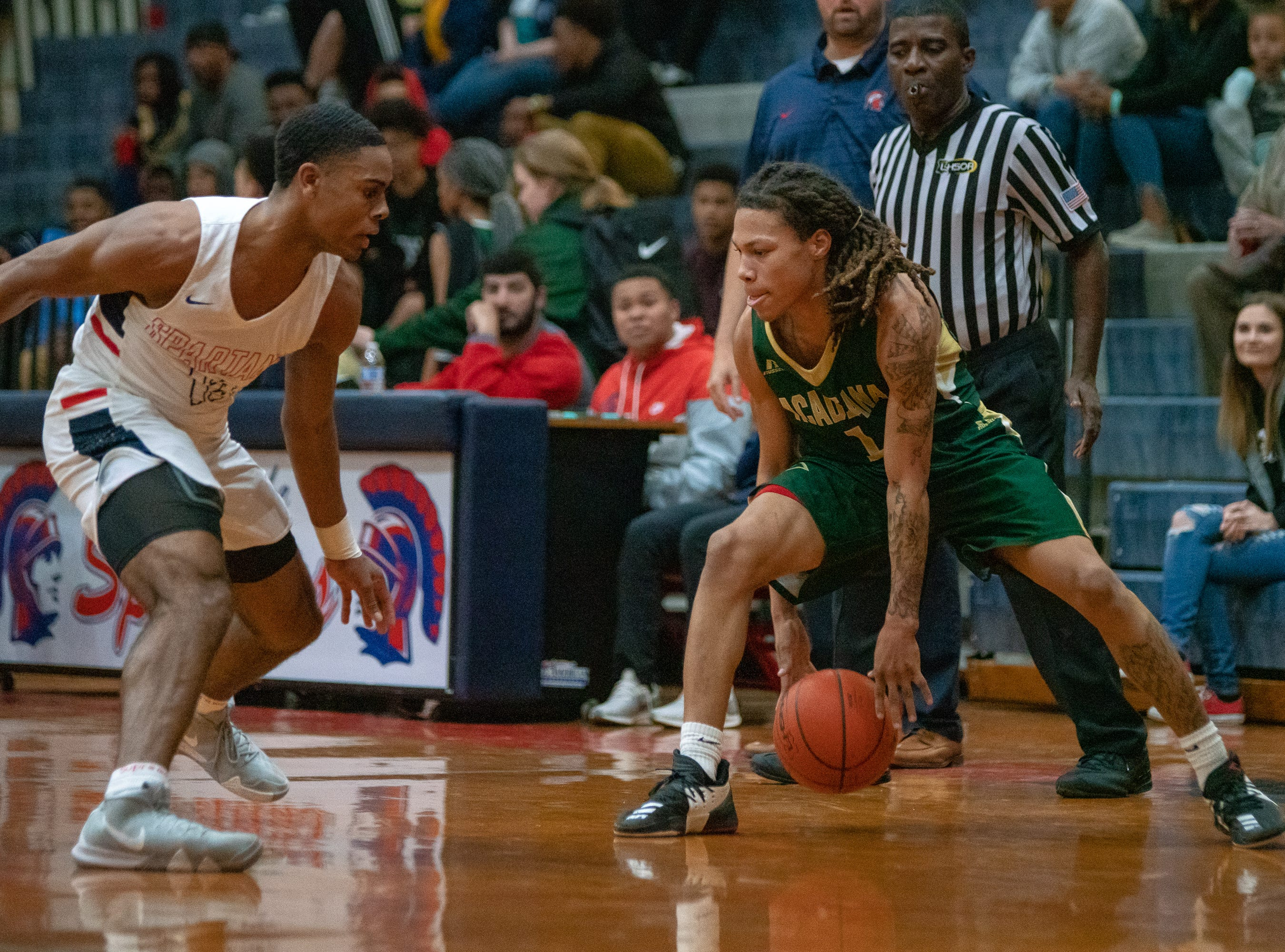 Acadiana High's Dentreal Mouton handles the ball on the court as the Comeaux High Spartans take on the Acadiana High Wreckin' Rams at Comeaux high school on Jan. 25, 2019.