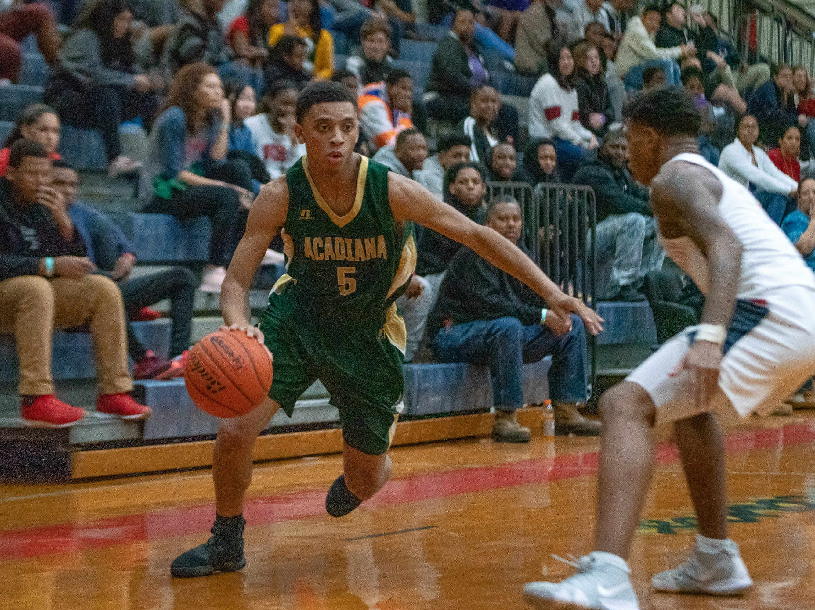 Acadiana High's Michael August (5) drives the ball to the basket as the Comeaux High Spartans take on the Acadiana High Wreckin' Rams at Comeaux high school on Jan. 25, 2019.