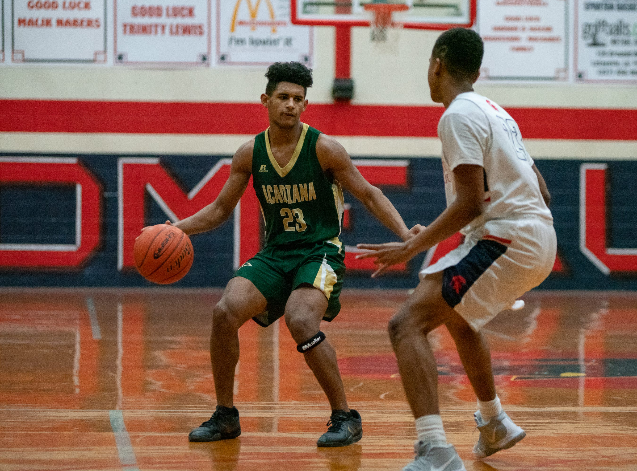 Acadiana High's Keontae Williams (23) handles the ball during the play as the Comeaux High Spartans take on the Acadiana High Wreckin' Rams at Comeaux High School on Jan. 25, 2019.