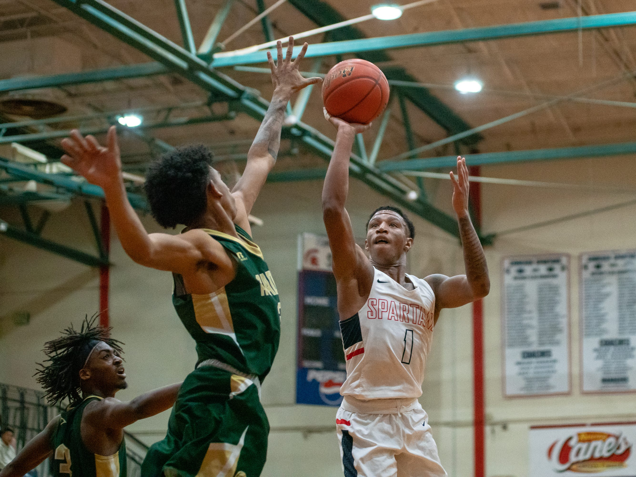 Comeaux High's Christian Archangel (1) goes up to the goal to score as the Comeaux High Spartans take on the Acadiana High Wreckin' Rams at Comeaux High School on Jan. 25, 2019.