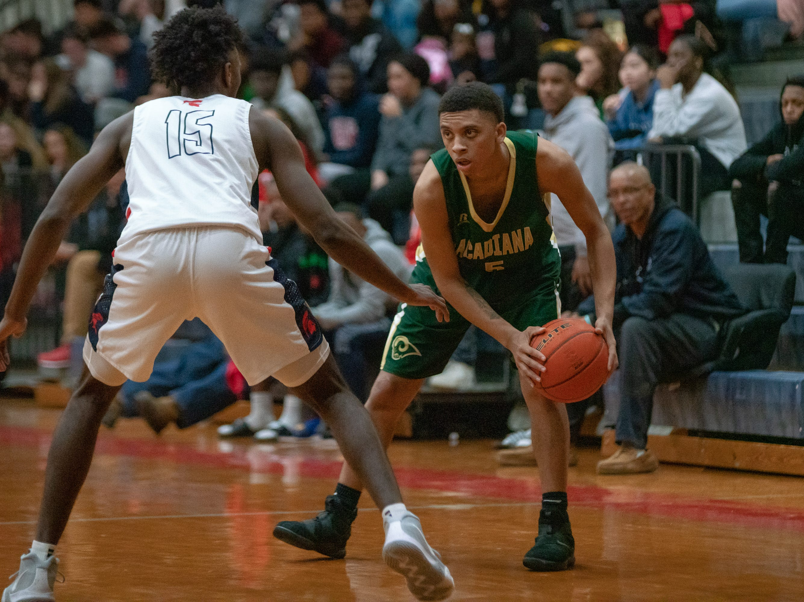 Acadiana High's Michael August (5) stares down his defender as the Comeaux High Spartans take on the Acadiana High Wreckin' Rams at Comeaux High School on Jan. 25, 2019.