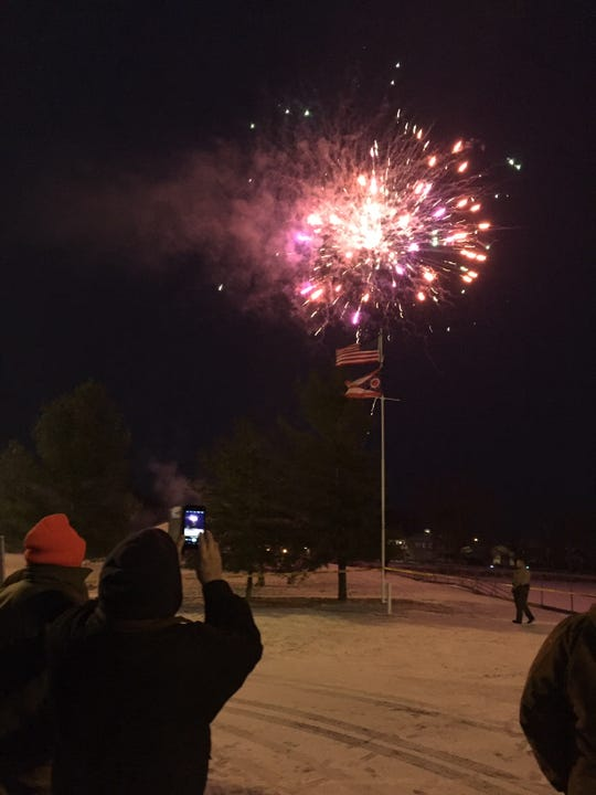People watch fireworks explode over Buckeye Lake Saturday morning to mark the start of the fifth annual Winterfest celebration.