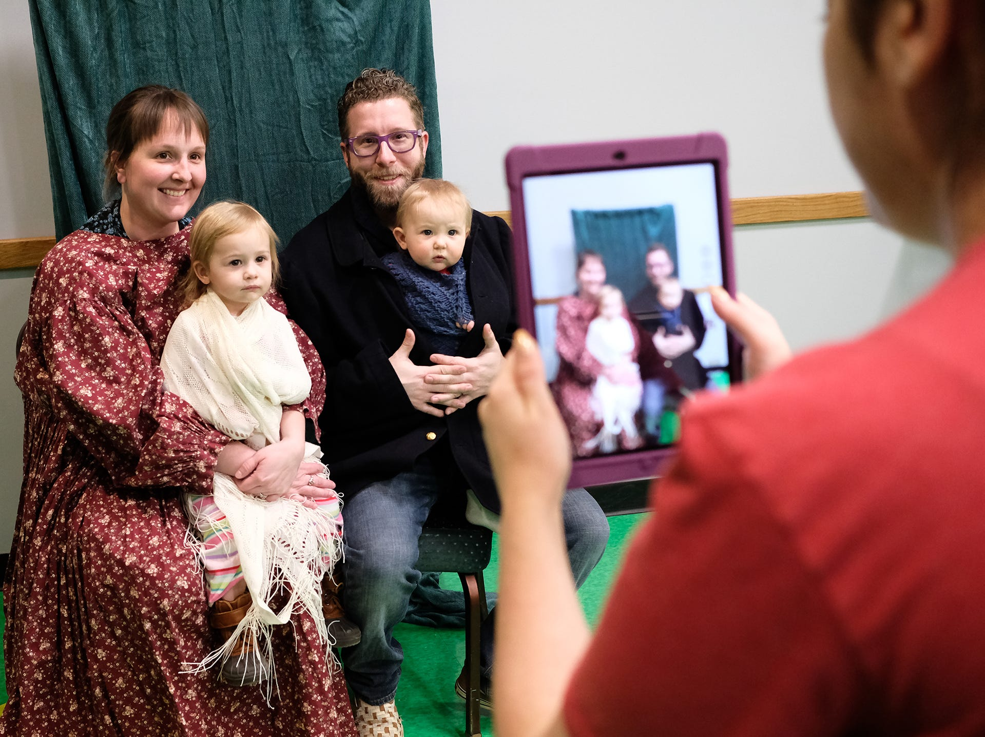Jack and Ashley Temsey from Potterville, and their two children Maesen, 2, and Charlotte, 10 months, have a photo taken with period clothing at a Statehood Day celebration event at the Michigan Library and Historical Center Saturday, Jan. 26, 2019. Michigan became a state on this day in 1837.