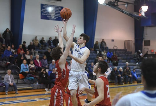 St. Peter's Caleb Stewart is surrounding by Redbirds as he gets off a shot in Friday's 54-32 Mid-Buckeye Conference victory over Loudonville in the Franciscan Center. Stewart scored a game-high 22 points, including 10 in the third quarter as the Spartans put the game out of reach.