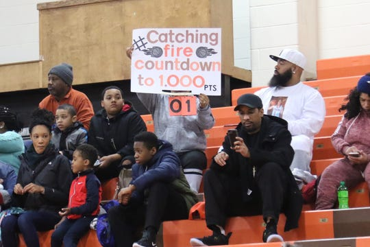 Talayzha Catchings' family hold up a sign counting down her journey to 1,000-career points on Saturday.